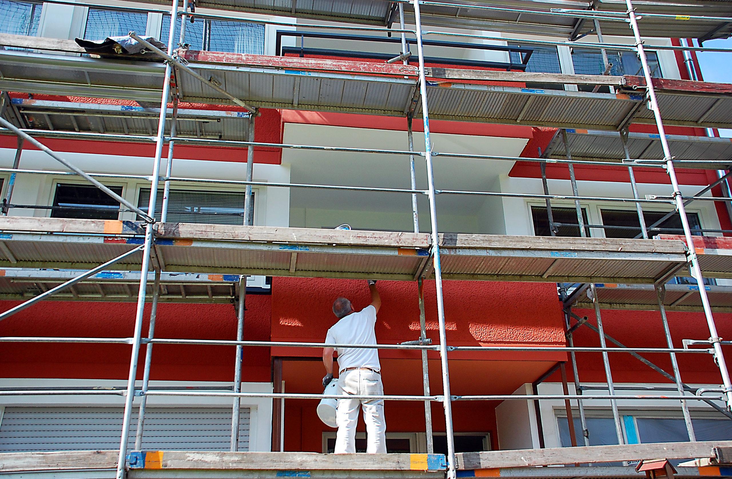 Maler auf Gerüst streicht die Außenfassade eines Mehrfamilienhauses